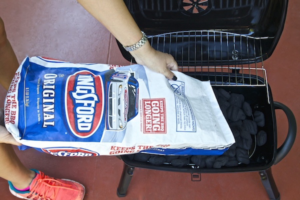 pouring Kingsford charcoal in grill