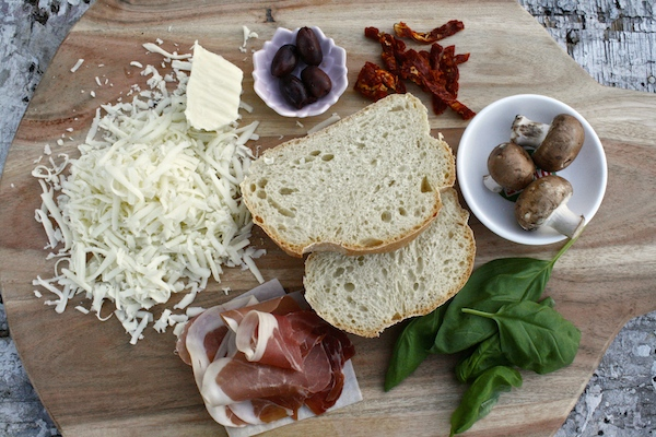Ingredients for cheese toast; Cacique Oaxaca cheese, olives, sun dried tomatoes, mushrooms, basil, and prosciutto