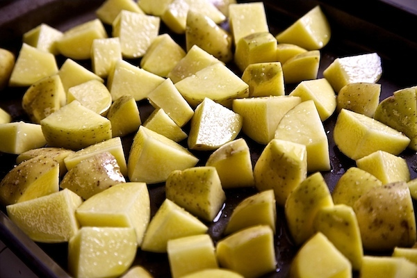 Yukon gold Idaho potatoes drizzled with olive oil and ready to be baked.