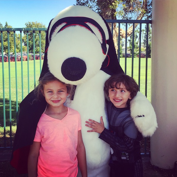 The kids pose with Snoopy in costume at Camp Spooky for Halloween.