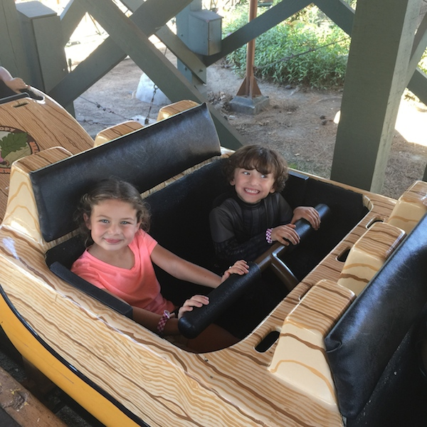 Kids on a roller coaster in Camp Spooky at Knott's Berry Farm
