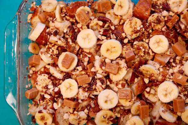 Pecans, almonds, caramel and banana slices layered on top of toasted croissant cubes for bread pudding.