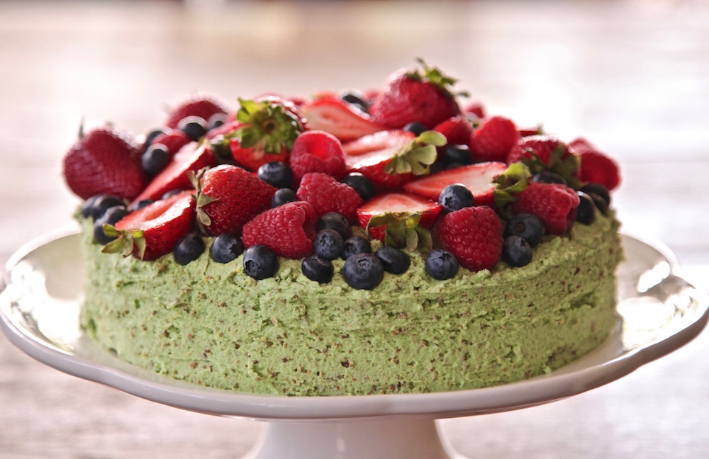 This olive oil cake is topped with pistachio buttercream and fresh berries. Perfect for Mother's Day or any occasion.