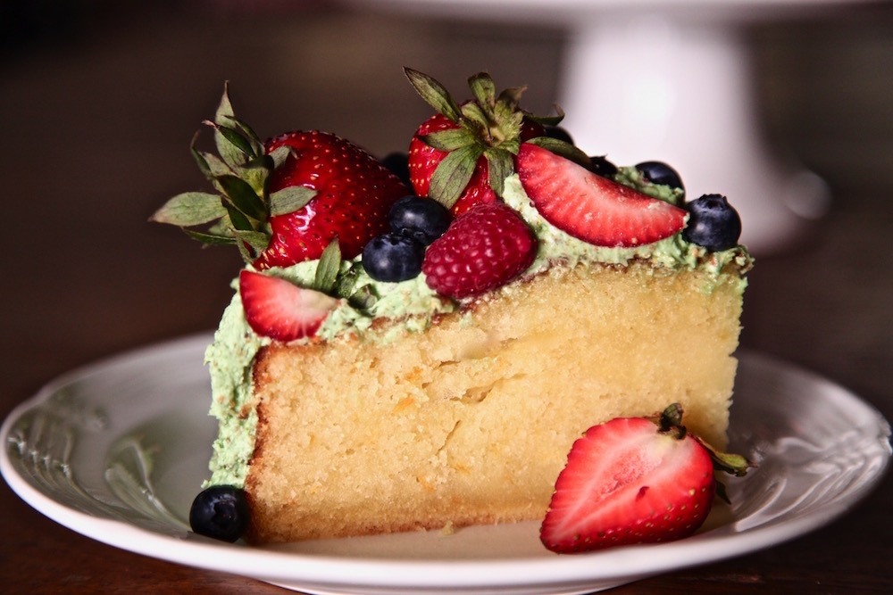 A small slice of olive oil pistachio buttercream berry cake.