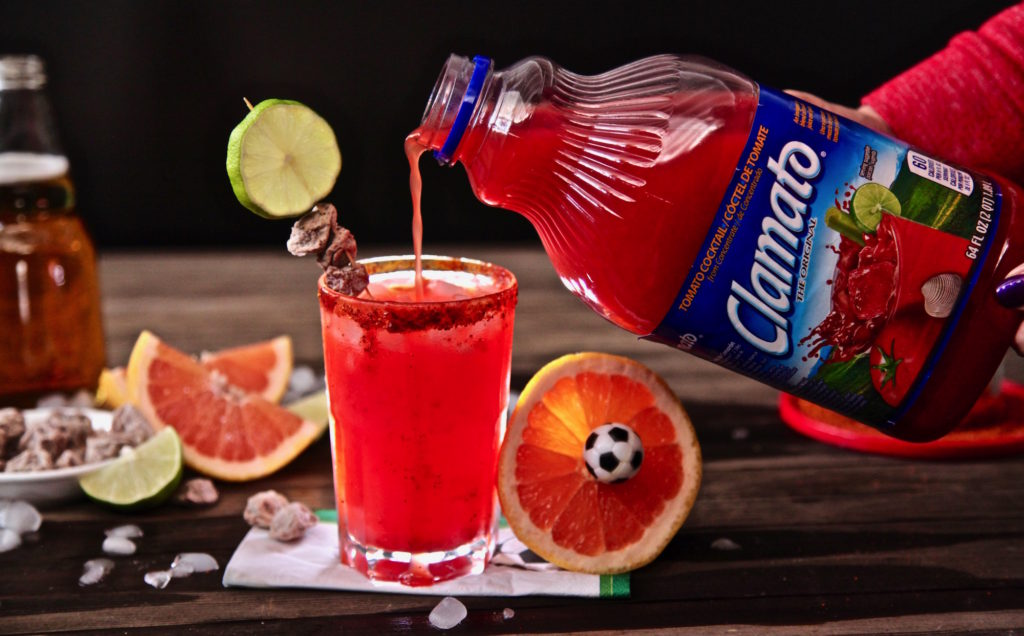 Pouring Clamato into Paloma Michelada