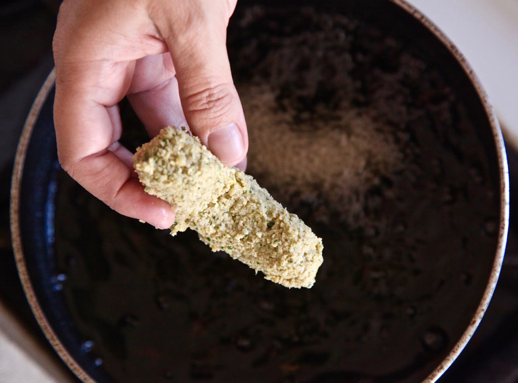falafel encrusted avocado slice about to be dropped in hot oil