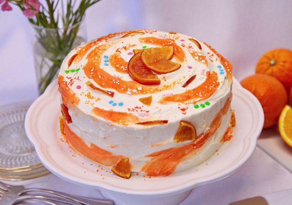 Moist Layer Orange Cake With Buttercream Frosting on a cake stand