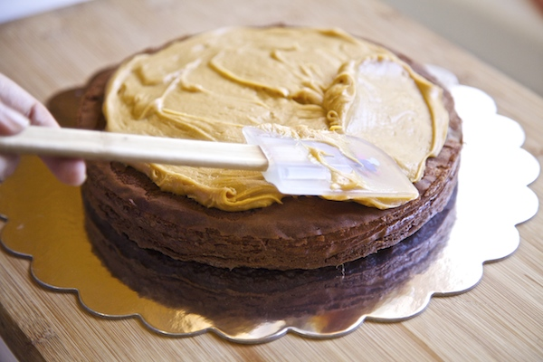 Spread peanut butter frosting on top of first layer of cake