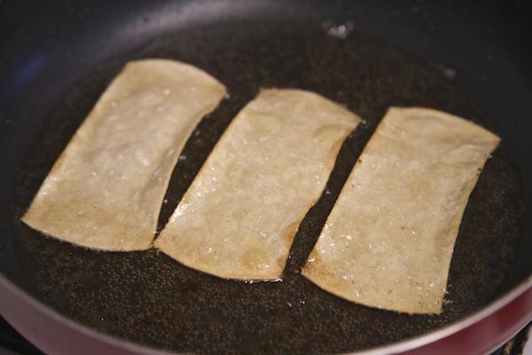 corn tortilla strips frying in oil til crisp
