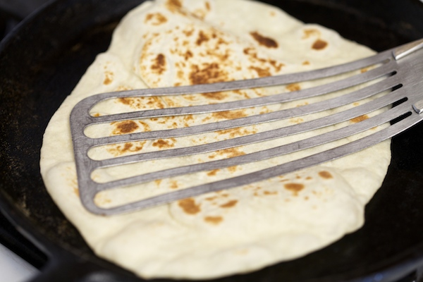 Pressing down on flour tortilla with a spatula #WMTMoms