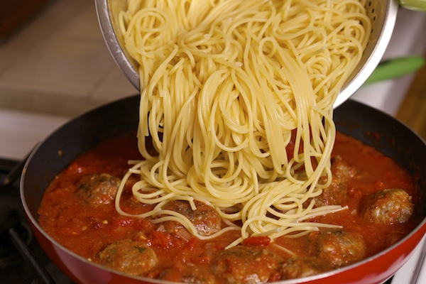 Barilla thick spaghetti being added to albondigas in a spicy chipotle sauce