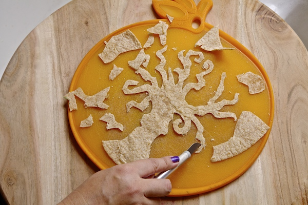 A wheat tortilla cut into the shape of a tree with x-acto knife