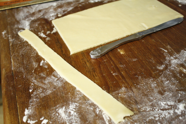 dough being cut into strips for bow tie cookies