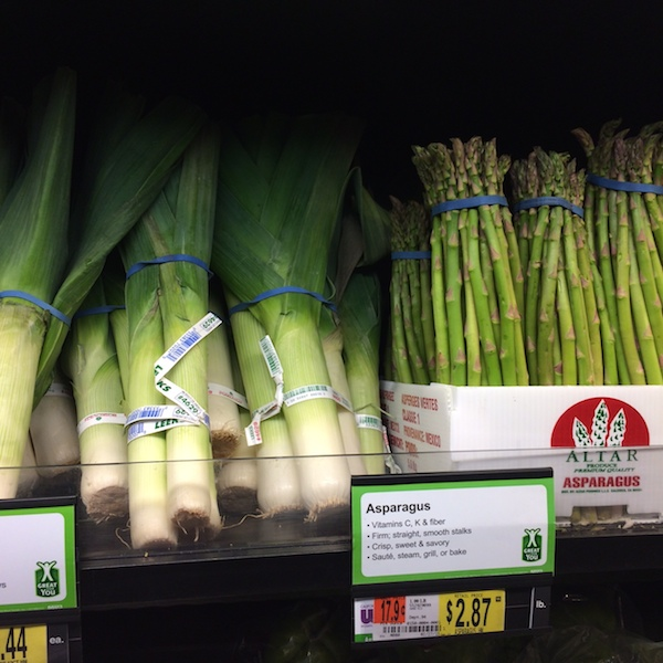 Leeks and asparagus sitting side by side at Walmart.