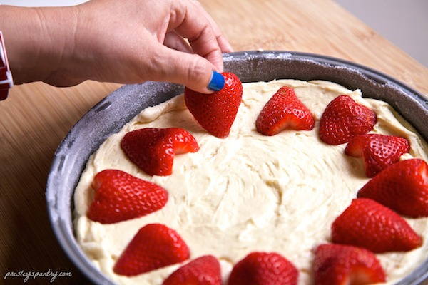 Line strawberries around the outer rim of the cake pan to form a ring.