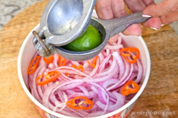 A lime being squeezed over the sliced onion and habaneros.