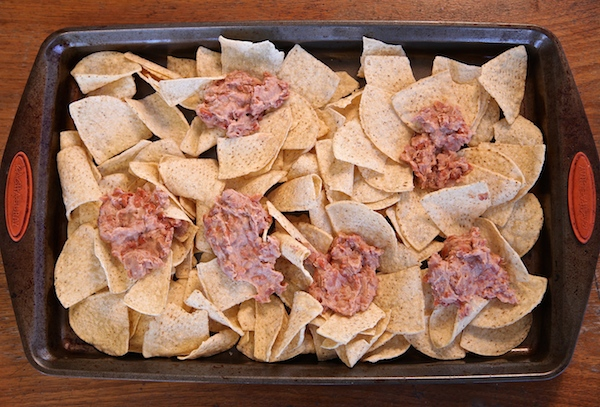 Refried beans on chips to make nachos