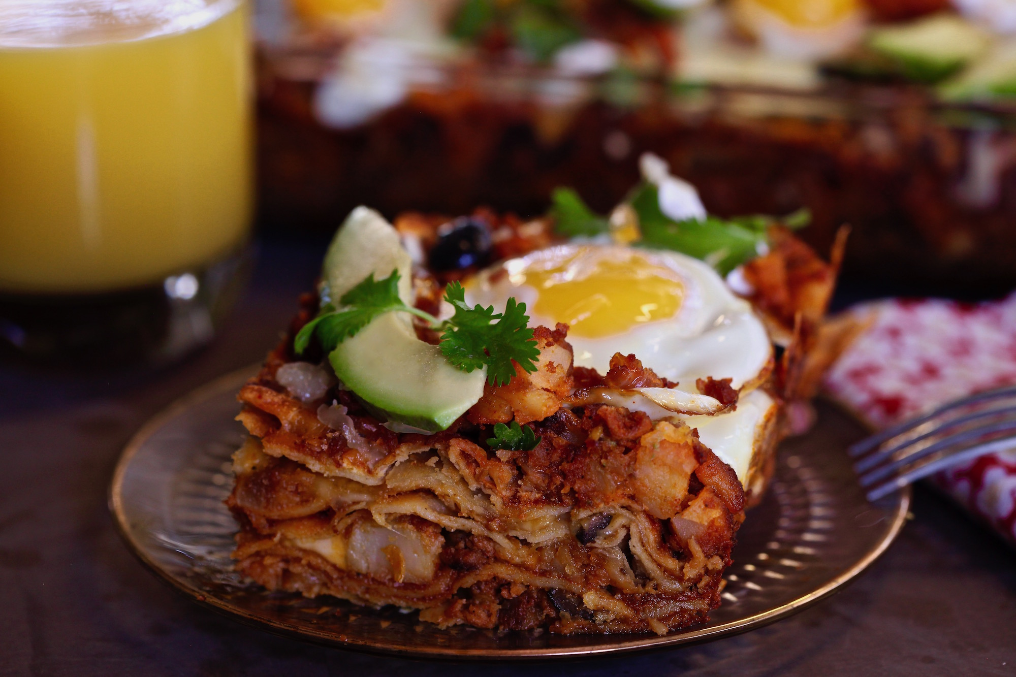 A slice of breakfast enchiladas from the tray with egg on top. All ingredients purchased at ALDI
