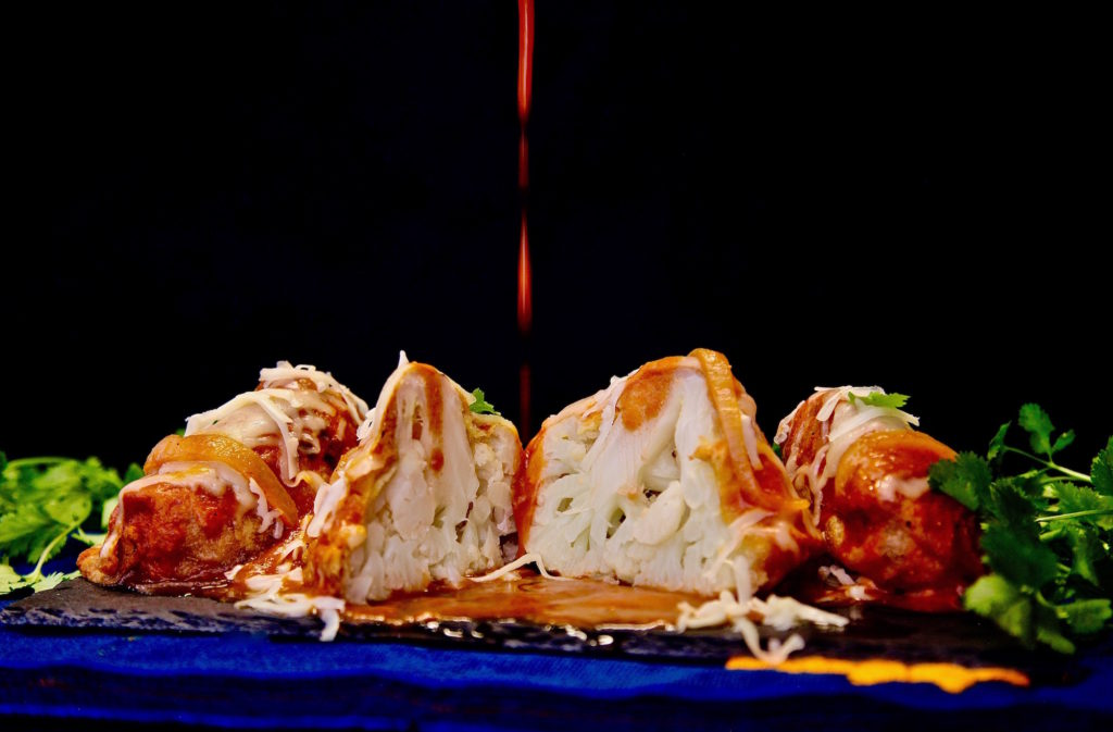 Cauliflower rellenos with spicy tomato sauce being poured over the top