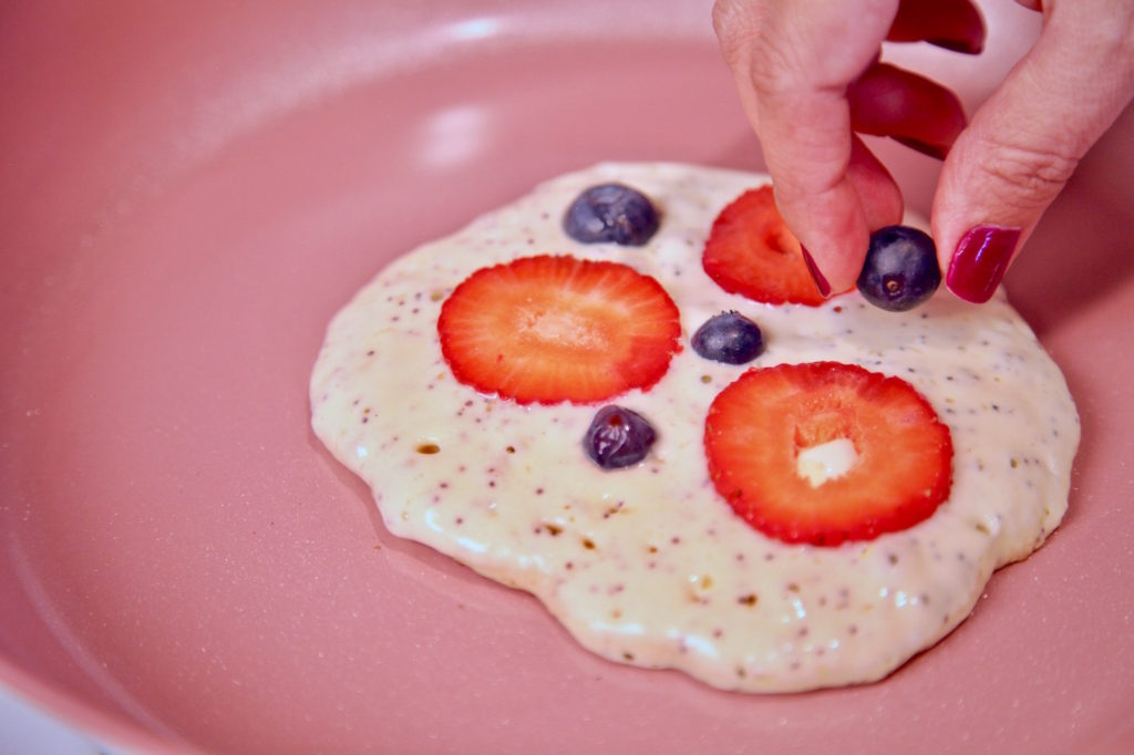 Adding berries to the Berry Poppy Seed Pancakes